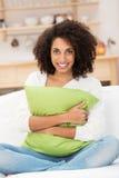 Härlig afrikansk amerikankvinna som kramar en kudde arkivbild