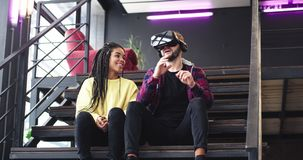 Härlig afrikansk dam och karismatisk grabb som spelar med exponeringsglas för en virtuell verklighet och tillsammans tycker om ti lager videofilmer