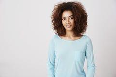 Härlig afrikansk flicka i blå skjorta som ler se kameran royaltyfri fotografi