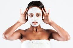 Härlig afrikansk kvinna i studio med den ansikts- maskeringen royaltyfri bild