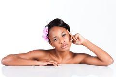 Härlig afrikansk kvinna i studion som gör kroppomsorg Royaltyfria Bilder