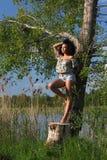 Härlig afrikansk kvinna med anseende för lockigt hår på ett träd Royaltyfri Fotografi