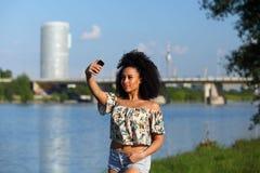 Härlig afrikansk kvinna med lockigt ta en bild med hennes telefon Royaltyfri Foto