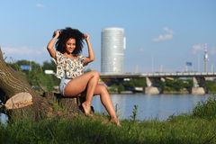 Härlig afrikansk kvinna med sammanträde för lockigt hår på en flodbank Arkivbilder