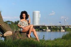 Härlig afrikansk kvinna med sammanträde för lockigt hår på en flodbank Royaltyfria Bilder