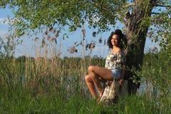 Härlig afrikansk kvinna med sammanträde för lockigt hår på ett träd Arkivfoton