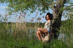 Härlig afrikansk kvinna med sammanträde för lockigt hår på ett träd Royaltyfria Bilder