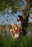 Härlig afrikansk kvinna med sammanträde för lockigt hår på ett träd Arkivfoto