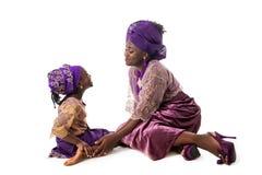 Härlig afrikansk kvinna och älskvärd liten flicka i traditionell klänning fotografering för bildbyråer