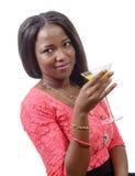 Härlig afrikansk kvinna som dricker orange fruktsaft royaltyfri fotografi
