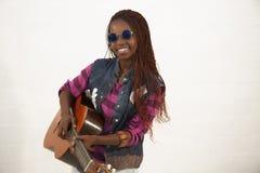 Härlig afrikansk kvinna som spelar gitarren arkivbild