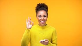 Härlig afrikansk kvinna som visar den ok gesten, online-shoppa applikation, grej arkivfoton