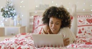 Härlig afro- amerikansk flicka som ligger på säng arkivfoton