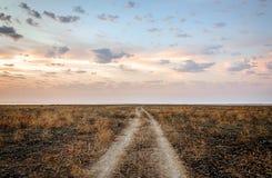 Härlig aftonhimmel för grusväg Arkivfoton