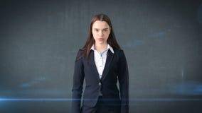 Härlig allvarlig affärskvinnastående, grå bakgrund Arkivfoto