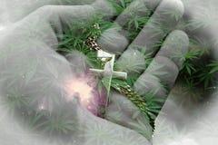 Härlig alternativ medicin Art With Marijuana Leaves, guld- religiöst kors i hand med nebulosabakgrund arkivbild