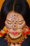 Härlig amazonian exotisk kvinna för Headshot med ansikts- målarfärg och svarta klänningen som allvarligt poserar för kamera, skog Royaltyfri Foto