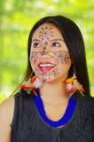 Härlig amazonian exotisk kvinna för Headshot med ansikts- målarfärg och svarta klänningen som poserar happilyforkameran, skogbakg Arkivfoto