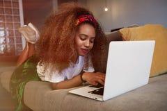 Härlig amerikansk afrikansk kvinna som skriver på bärbara datorn, smsande vänner via sociala nätverk Studentflicka som bläddrar i arkivfoton