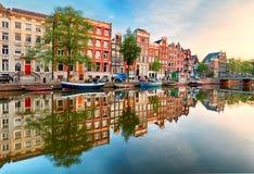 Härlig Amsterdam solnedgång Typiska gamla holländarehus på bron och kanalerna i vår, Nederländerna royaltyfri foto