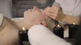 härlig ansiktsbehandling som får massagekvinnan Fingermassage med olja på skönheten Spa arkivfilmer