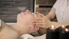 härlig ansiktsbehandling som får massagekvinnan Fingermassage med olja på skönheten Spa stock video