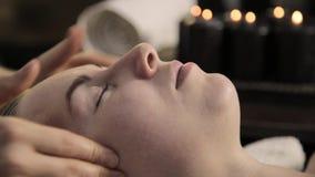 härlig ansiktsbehandling som får massagekvinnan Fingermassage med olja på skönheten Spa lager videofilmer