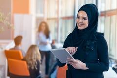 Härlig arabisk flicka med minnestavladatoren som arbetar på det startup kontoret arkivfoton