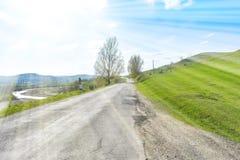 Härlig asfalterad väg på den stora gröna kullen i en solig sommardag royaltyfria foton