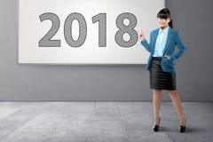 Härlig asiatisk affärskvinna med markören som skriver nummer 2018 Arkivfoto