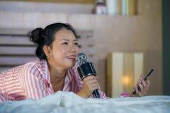 Härlig asiatisk amerikansk tonåringflicka som sjunger karaokesång den upphetsade hemmastadda sovruminnehavmobiltelefonen som spel arkivbild