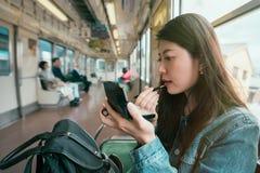 Härlig asiatisk dam som sätter på läppstift arkivfoton