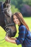 Härlig asiatisk Eurasianflicka med hennes häst royaltyfria bilder