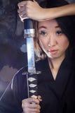 Härlig asiatisk flicka i kimono med en katana Fotografering för Bildbyråer