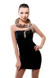Härlig asiatisk flicka i lite den svarta klänningen som rymmer en orm royaltyfri foto
