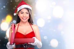 Härlig asiatisk flicka med gåvan för jul för öppning för hatt för santa ` s Arkivbilder