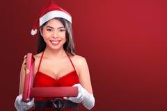 Härlig asiatisk flicka med gåvan för jul för öppning för hatt för santa ` s Arkivfoton