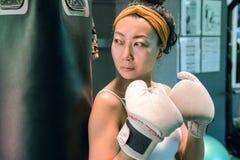 Härlig asiatisk flicka med vita boxas handskar som står nära ett päron i idrottshallen arkivbilder