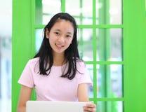 Härlig asiatisk flicka som ler och använder bärbar datordatoren Arkivfoto