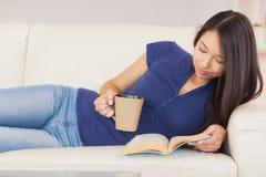 Härlig asiatisk flicka som ligger på soffan som läser en roman och dricker den varma drycken Royaltyfri Bild