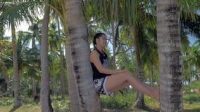 H?rlig asiatisk flicka som lutar mot palmtr?dstammen p? den tropiska stranden arkivfilmer