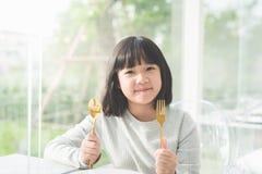 Härlig asiatisk flicka som rymmer en sked och en gaffel Arkivbild