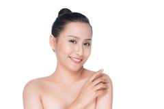 Härlig asiatisk flicka som slår hennes sunda hud som isoleras på vit Royaltyfri Bild