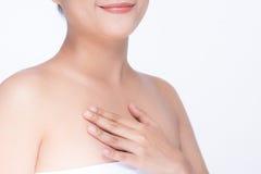 Härlig asiatisk flicka som slår hennes sunda hud som isoleras på vit Arkivfoton