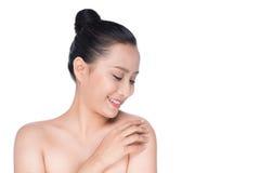 Härlig asiatisk flicka som slår hennes sunda hud som isoleras på vit Arkivfoto