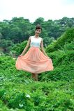 Härlig asiatisk flicka som spelar i gräset arkivfoton
