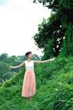 Härlig asiatisk flicka som spelar i gräset arkivbilder