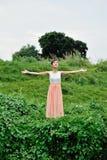 Härlig asiatisk flicka som spelar i gräset royaltyfri foto