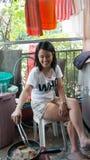 Härlig asiatisk flickamatlagning utomhus, dagen som in steker, wokar mat Arkivfoto