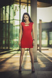 Härlig asiatisk flickamodell i den röda klänningen som poserar på den moderna glass stilstadsbakgrunden solig dag Arkivfoton